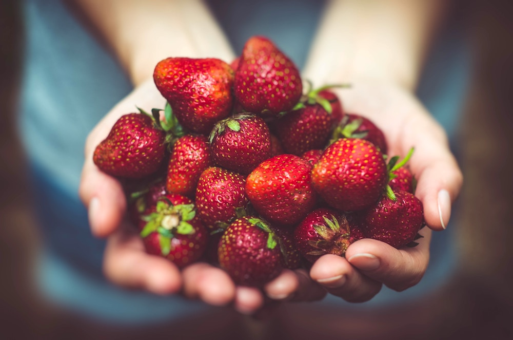 Woman Holding Heeps of Strawberries in Her Hands