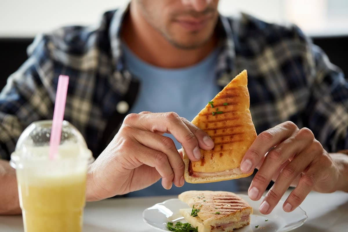 close up of man eating sandwich at cafe for lunch