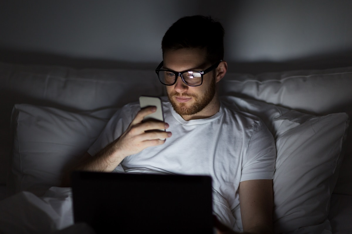 man with laptop and smartphone at night in bed